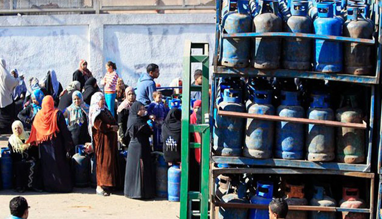 Citizens wait in line to buy gas cylinders at a distribution point in Cairo